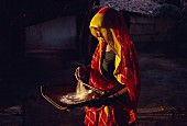 An Indian woman washing rice for an evening meal, Gujarat, India