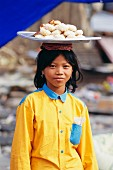 A girl wearing a yellow shirt carrying a platter of freshly baked rolls on her head, Phnom Penh, Cambodia