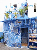 A blue-and-white artist's shop decorated with handprints in the Medina of Asilah, Morocco