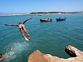A boy diving from a rock into the sea with fishing boats in the background, Larache, Morocco