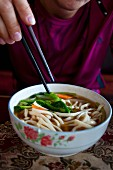 A woman eating noodle soup, Lhasa, Tibet, China, Asia