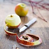 Äpfel, teilweise geschält, auf Holztisch