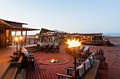 Wolwedans, NamibRand Privatreservat, Namibia, Afrika - 'Dunes Lodge' mit Fackeln und Feuerschale im Abendlicht