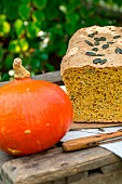 Pumpkin bread with pumpkin seeds and a Hokkaido pumpkin on a wooden crate