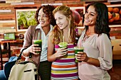 Three women drinking juice together in cafe