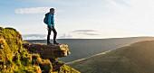 Junger Wanderer auf Felsvorspung mit Panoramaausblick