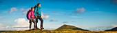 Zwei junge Wanderer auf grasbewachsenem Hügel
