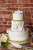A three tiered wedding cake on a table in front of a red brick wall