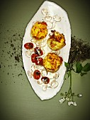 Potato cakes on mushroom carpaccio with fried tomatoes
