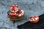 Pomegranate halves in a metal dish and next to it