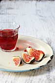 A glass of red wine and fresh figs on a plate