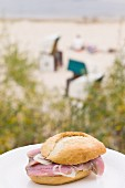 A soused herring roll with the Heringsdorf beach in the background, Usedom