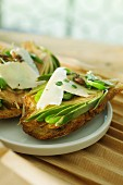 Crostini topped with artichokes, fava beans, Parmesan cheese and anchovy sauce