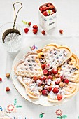 Waffles with icing sugar and wild strawberries
