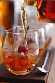 Whiskey with ice cubes and a cherry