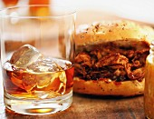 A pulled pork sandwich and a glass of rum