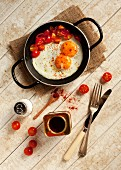 Two fried eggs and fried, chopped tomatoes sprinkled with paprika in a pan