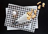 Papiertüte mit Salzgebäck in der Form von Fish & Chips mit Salz und Essig