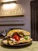 A tomato, mozzarella and basil sandwich in a kitchen