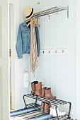 Offene Garderobe mit Ablage, auf Haken Jeansjacke und Strohhut, auf Metallbank Schuhe, vor Holzwand
