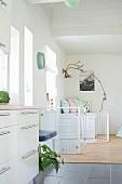 Blick von Küchenzeile auf schmalen Treppenaufgang und Leseplatz mit Hirschgeweih im Hintergrund