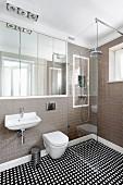 Designerbad mit eingebautem Spiegelschrank, seitlich bodenebener Duschbereich mit Glas Trennwand, auf Fliesenboden geometrisches Muster