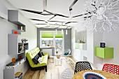 Schmales Wohnzimmer mit hellgrauem Zick-Zack-Regal und grünem Sofa; im Vordergrund Essplatz