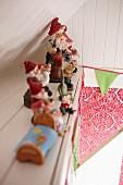 Zwergenparade auf Absatz in einer holzverschalten Dachschräge, bunte Wimpelgirlande und florales Muster im Hintergrund