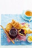 Rote Traubenmarmelade mit frischen Croissants, Butter und Tasse Tee