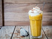 A pumpkin spice smoothie with whipped cream