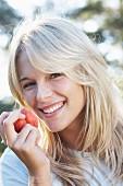 A smiling woman eating a peach