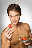 A young, topless man holding a large strawberry