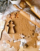 Rolled-out gingerbread biscuit pastry with cutters and cut-out biscuit shapes