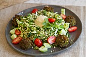 Bulgur salad with falafel, hummus, dandelion, kale, Chinese cabbage, cucumbers, tomatoes and mint