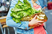 A woman carrying a lettuce in her handbag