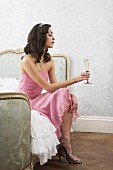 A woman sitting on a bed with a glass of champagne