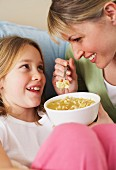 A mother and daughter eating chicken noodle soup