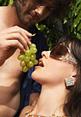 A man feeding a woman grapes