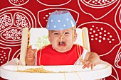 A crying baby in a high chair with a bowl of spaghetti on his head