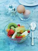 Fruit salad, eggs, salt and pepper on a breakfast table