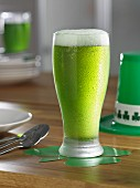 A glass of green beer on a table