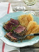 Tuna fish with sesame and poppy seeds served with fried rice vermicelli