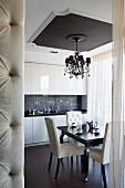 Kronleuchter an Kassettendecke in eleganter Wohnküche; Raumteiler-Ecke mit Polsterknöpfen im Vordergrund