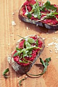 Slices of bread topped with beetroot spread and rocket