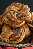 Chocolate and cinnamon buns with icing sugar on a pewter stand