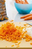 Grated carrots and diced onions on a cutting board