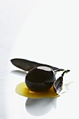 A black olive in a puddle of olive oil