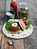 A chickpea burger with yogurt and gherkins