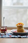 A stack of pancakes with pomegranate seeds for Christmas Day breakfast
