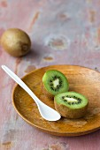 Kiwi, halbiert, auf Holzteller